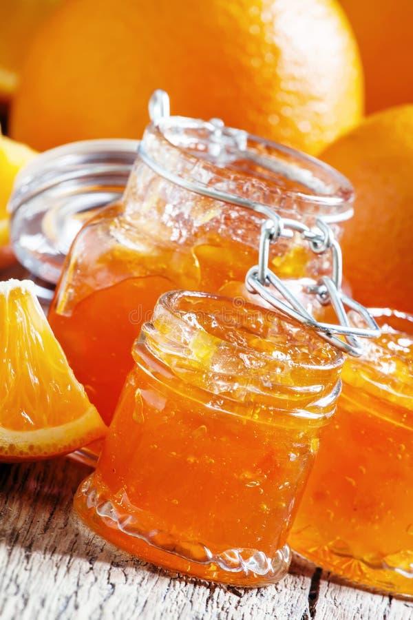 Doce alaranjado caseiro saboroso e laranjas frescas, parte traseira de madeira do vintage fotos de stock