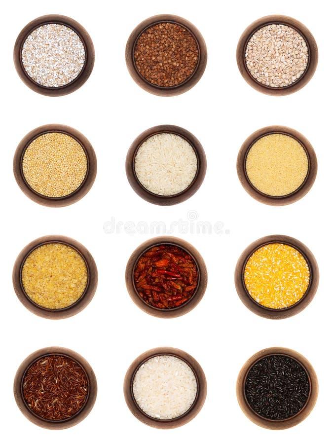 Doce cereales diferentes en los tazones de fuente de madera, aislados fotografía de archivo libre de regalías