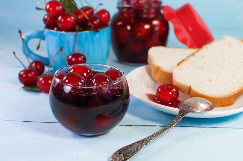 Doce de cereja e pão deliciosos do brinde Em uma superfície de madeira azul imagem de stock royalty free