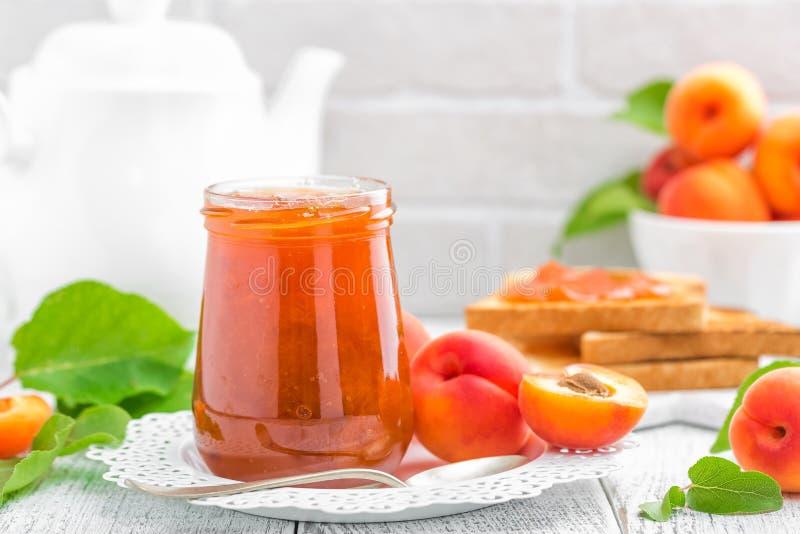Doce do abricó em um frasco e em uns frutos frescos fotografia de stock