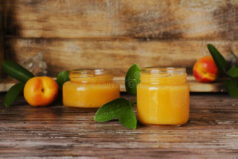 Doce em uns frascos de vidro pequenos com frutos, foco seletivo do abricó imagens de stock