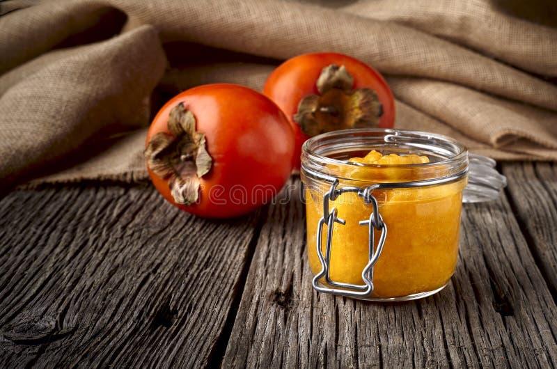Doce ou doce de fruta do caqui no frasco de vidro no fundo de madeira - fim acima da fotografia fotografia de stock