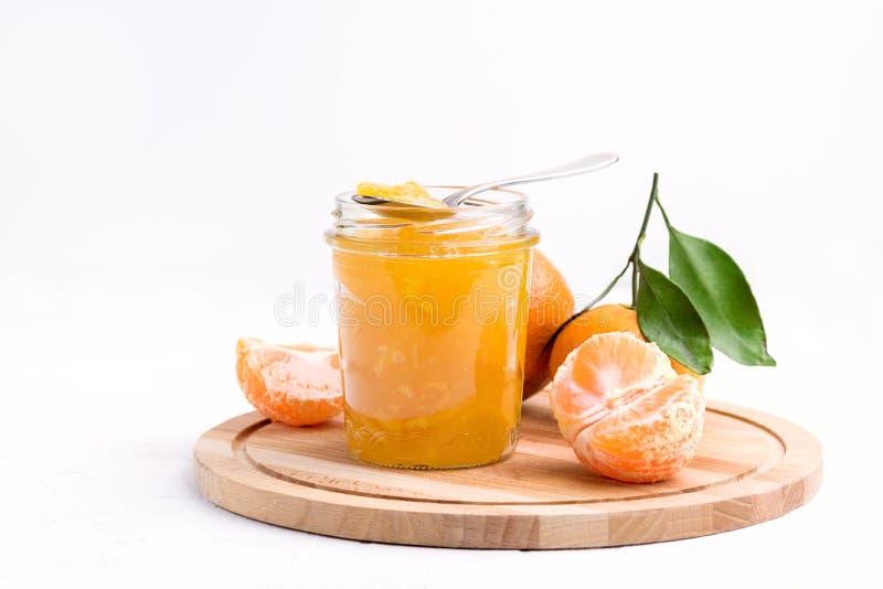 Doce saboroso do mandarino do citrino em um confiture branco do citrino do espaço da cópia do fundo do frasco de vidro fotos de stock royalty free