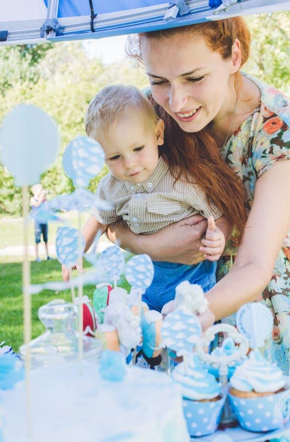 Doce-tabela O bebê come o bolo de aniversário com mãos Sua mãe toma-o Festa de anos no parque no piquenique imagem de stock