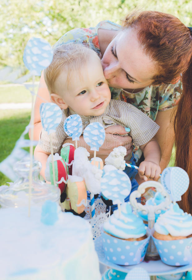 Doce-tabela O bebê come o bolo de aniversário com mãos Sua mãe toma-o Festa de anos no parque no piquenique fotografia de stock