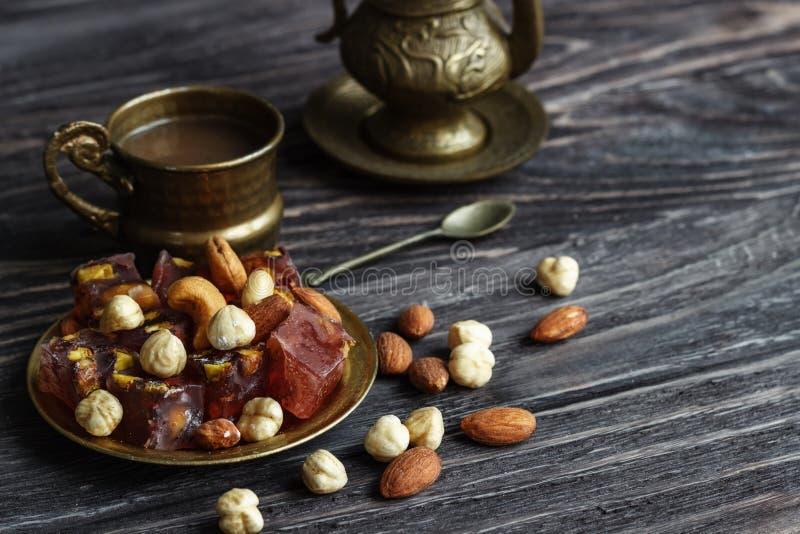 Doces árabes orientais com as porcas diferentes um a xícara de café Doces orientais Lokum tradicional de Rahat do loukoum em um d foto de stock