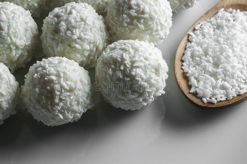 Doces brancos da bola do chocolate com cobertura e cocos do coco na colher na placa branca fotografia de stock
