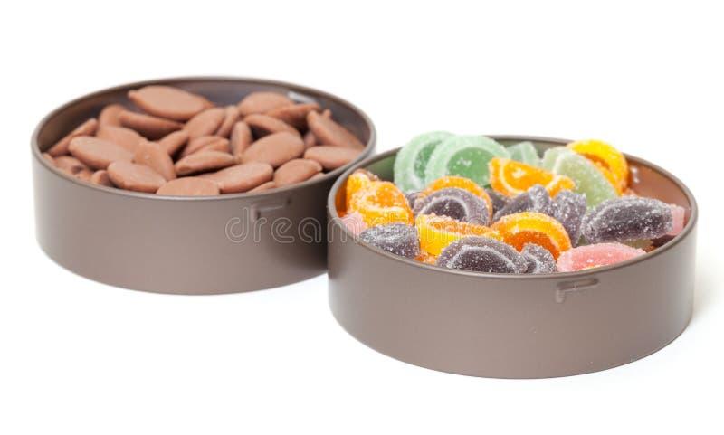 Doces coloridos da geléia e de chocolate em umas latas de estanho fotografia de stock royalty free