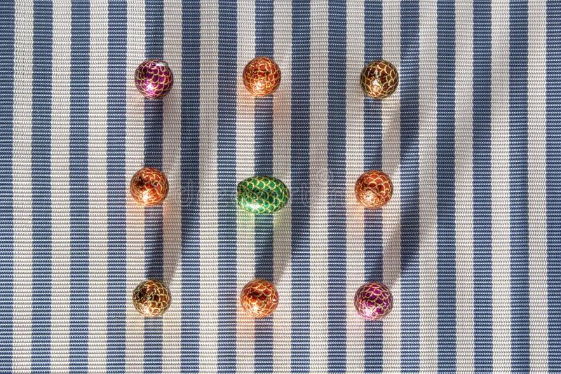 Doces coloridos dos doces em fundo listrado Ovos da sobremesa do chocolate - tradição feliz da Páscoa imagens de stock