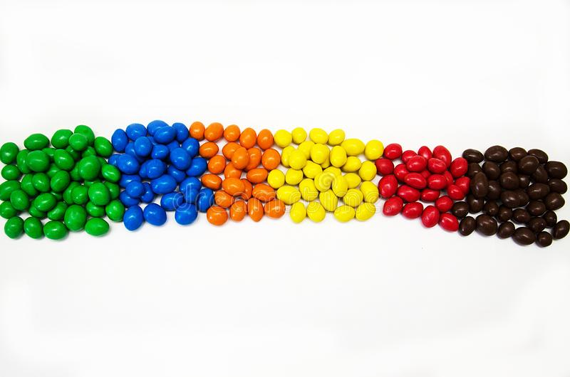 Doces coloridos espalhados para fora pela cor, vista superior, em um fundo branco foto de stock royalty free