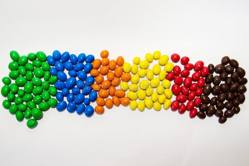 Doces coloridos espalhados para fora pela cor, vista superior, em um fundo branco fotos de stock