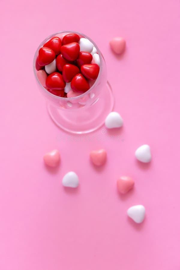 Doces coloridos ou comprimidos na forma dos corações no vidro do wie O dia de Valentim do conceito ou a medicina, farmácia, cardi fotografia de stock royalty free