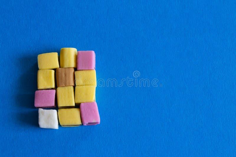 Doces coloridos saborosos no fundo azul foto de stock royalty free