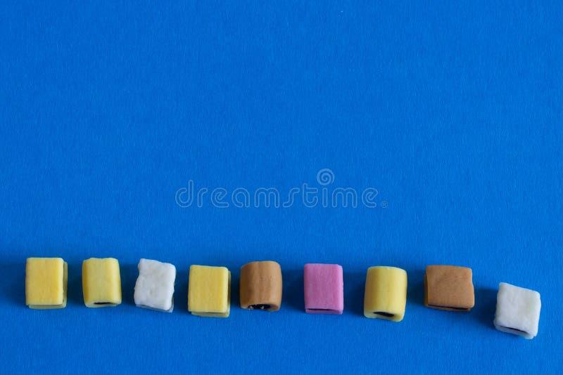 Doces coloridos saborosos no fundo azul imagem de stock royalty free