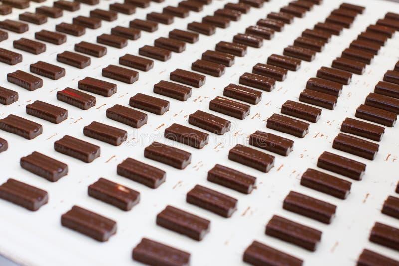Doces com cobertura em chocolate em uma fábrica dos doces imagens de stock