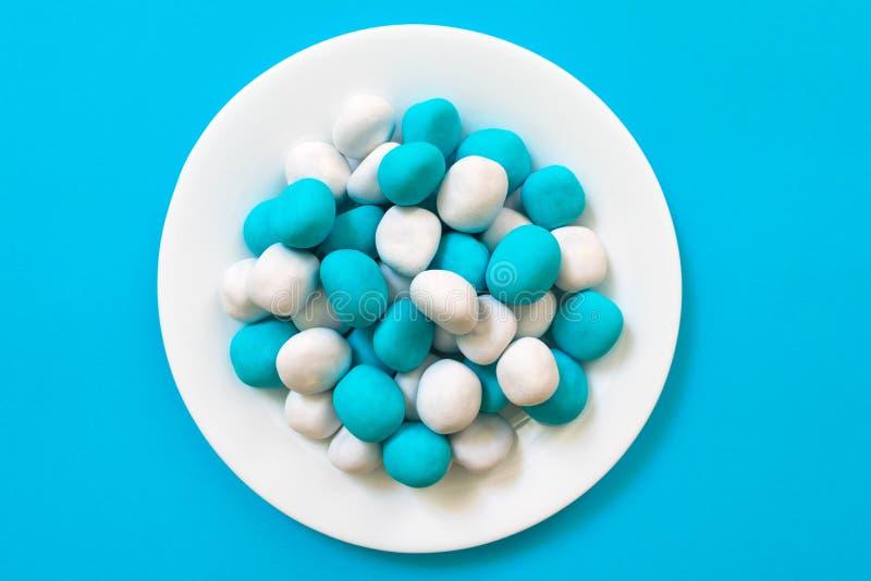 Doces - cookies da cor branca e azul sob a forma de uma pedra do mar em uma placa branca em um fundo azul foto de stock royalty free