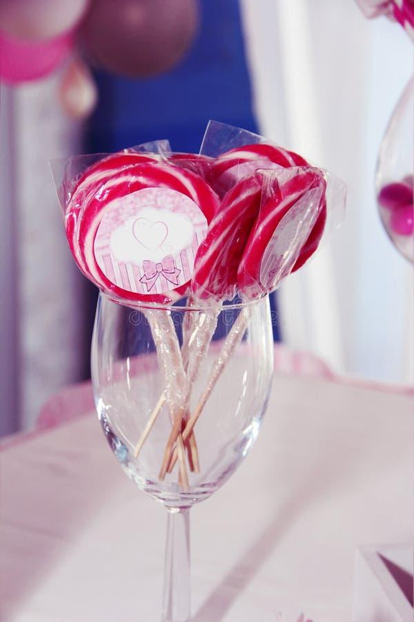 Doces cor-de-rosa doces em uma vara em um vidro para decorar a tabela festiva imagem de stock