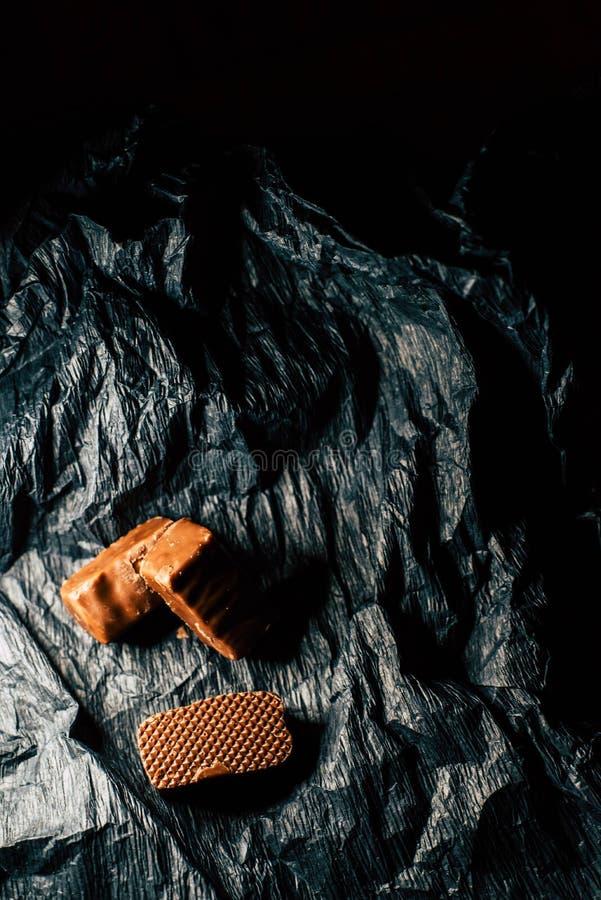 Doces de chocolate em um fundo preto fotografia de stock royalty free