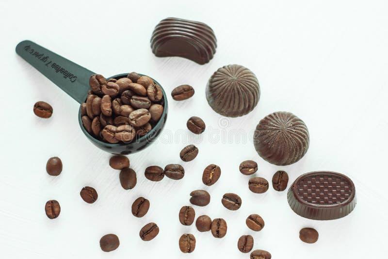 Doces de chocolate escuros, doces com uma colher de feijões de café no fundo claro Conceito do estilo de vida imagens de stock royalty free