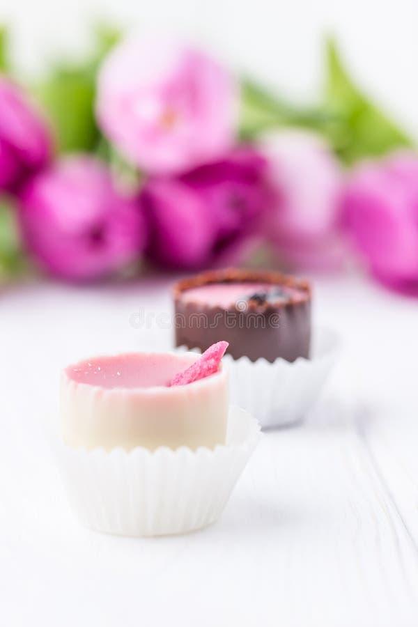 Doces de chocolate feitos à mão e tulipas cor-de-rosa em um fundo branco Espaço livre fotografia de stock royalty free