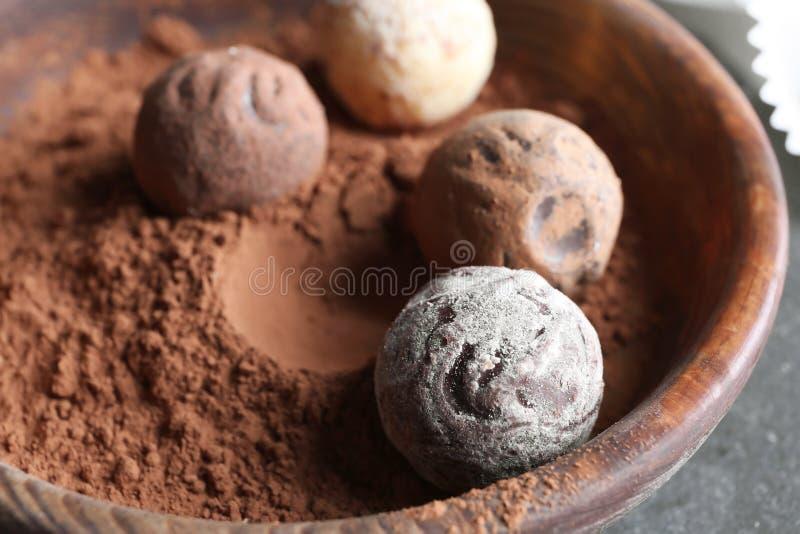 Doces de chocolate na bacia com pó de cacau, close up fotos de stock royalty free
