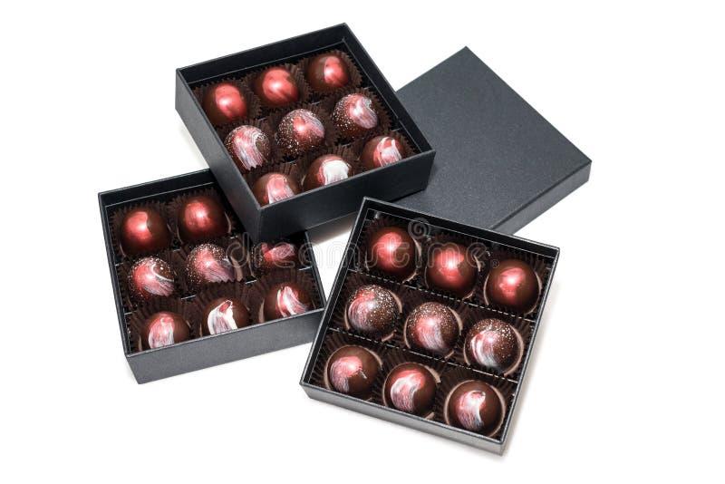 Doces de chocolate nos giftboxes isolados no fundo branco Confeitos sortidos dos chocolates em suas caixas de presente Grupo de c fotografia de stock royalty free