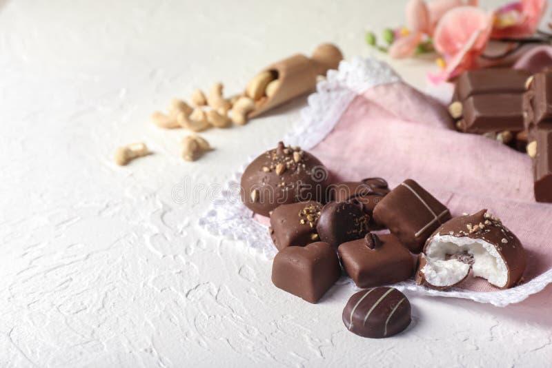Doces de chocolate saborosos no fundo textured branco imagens de stock