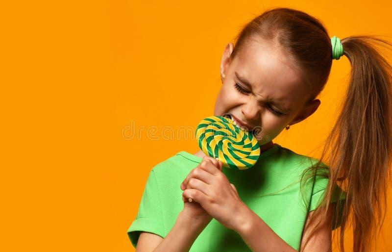 Doces doces do lollypop da mordida nova feliz da criança da menina da criança pequena fotografia de stock