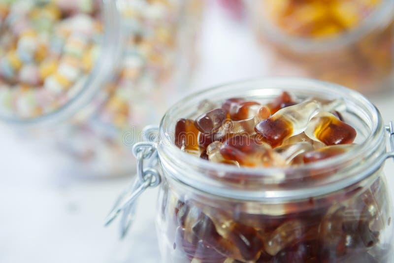 Doces dos doces, doces da geleia da coca em um frasco imagens de stock