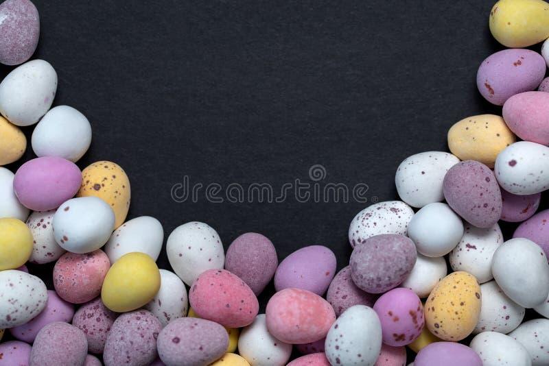 Doces dos ovos da páscoa coloridos no fundo preto foto de stock