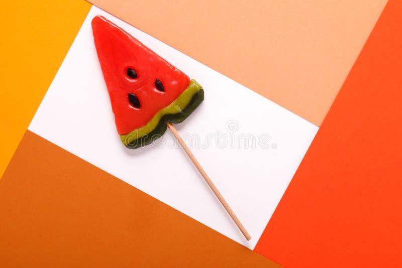Doces em uma vara em um quadro de um cartão multi-colorido fotografia de stock royalty free