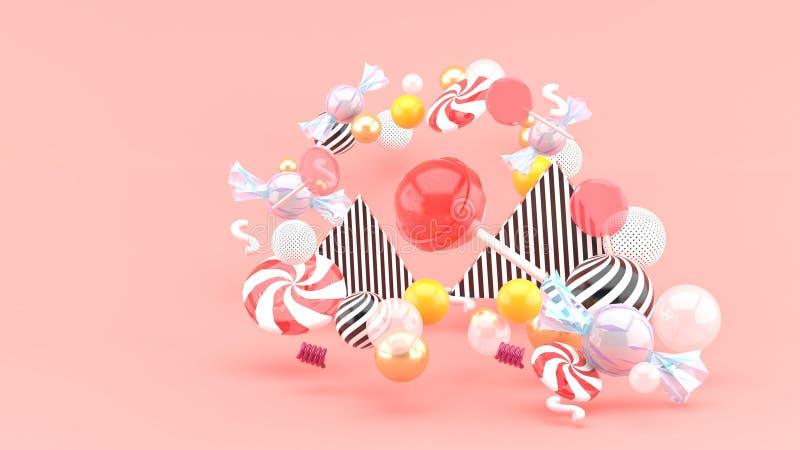 Doces entre bolas coloridas no fundo cor-de-rosa imagens de stock