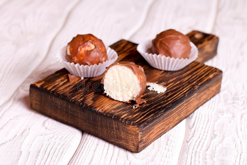 Doces feitos a mão do coco do chocolate na tabela de madeira imagens de stock