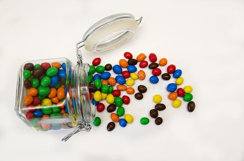 Doces multicoloridos no isolado de vidro dos frascos no fundo branco imagens de stock royalty free