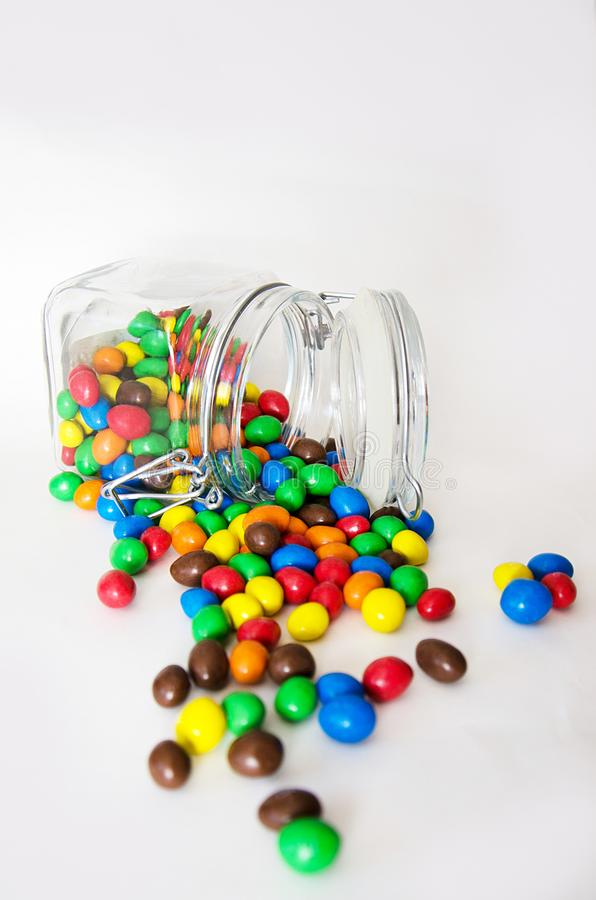 Doces multicoloridos no isolado de vidro dos frascos no fundo branco fotografia de stock