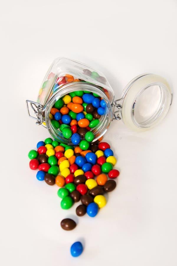 Doces multicoloridos no isolado de vidro dos frascos no fundo branco foto de stock royalty free