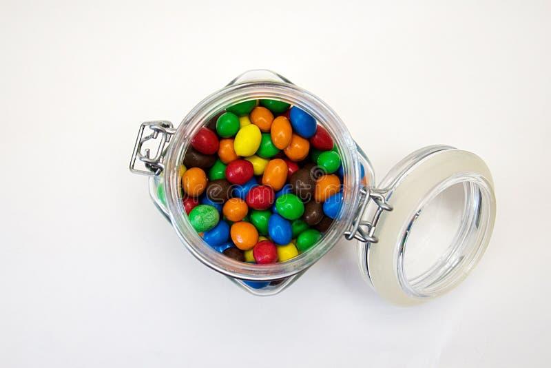 Doces multicoloridos no isolado de vidro dos frascos no fundo branco foto de stock