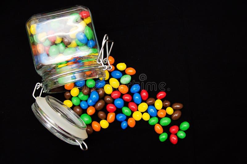 Doces multicoloridos no isolado de vidro dos frascos no fundo preto fotos de stock royalty free