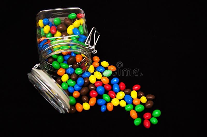 Doces multicoloridos no isolado de vidro dos frascos no fundo preto fotografia de stock royalty free