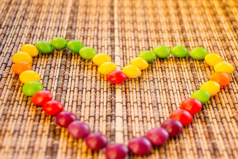 Doces que formam uma forma do coração bombom colorido no guardanapo da palha como um coração Textura de bambu da esteira do guard imagem de stock royalty free