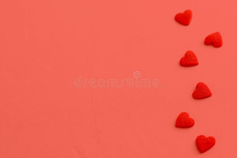 Doces vermelhos do coração da textura do velure dispersados no fundo coral Arranjo do quadro da beira Caridade romance do dia de  fotos de stock