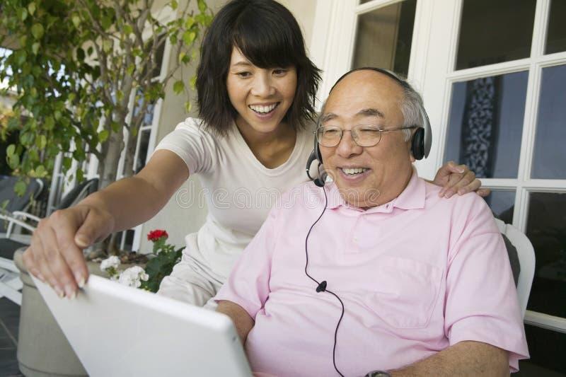 Dochter Bijwonende Vader In Using Laptop bij Portiek stock afbeelding