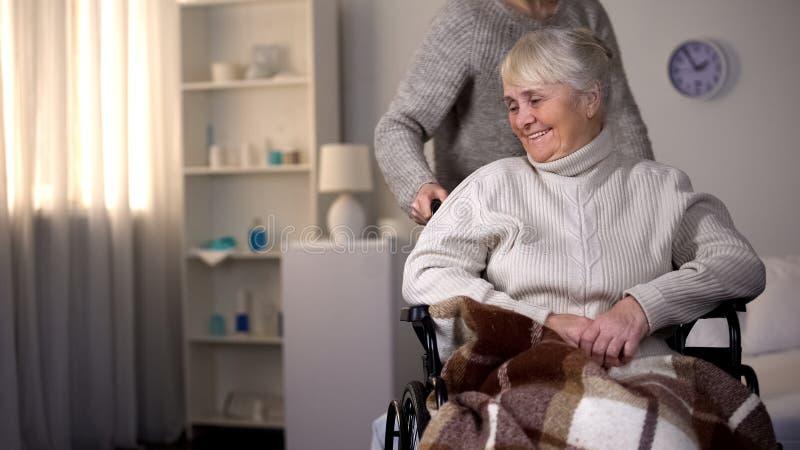 Dochter die bejaarde moeder in rolstoel, verzorger behandelen die pati?nt helpen stock fotografie
