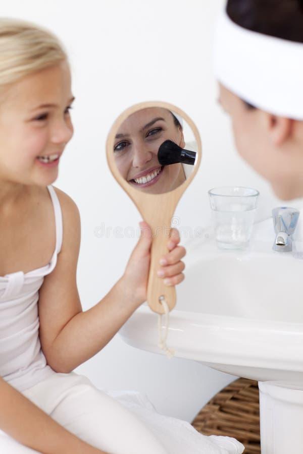 Dochter die een spiegel en moedermake-up houdt stock foto