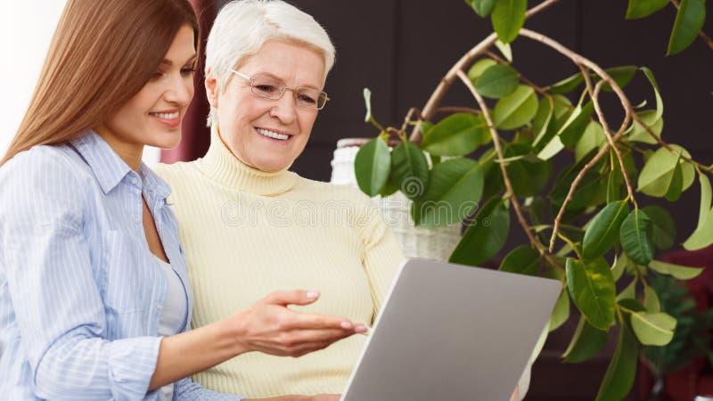Dochter die haar hogere moeder onderwijzen die laptop met behulp van royalty-vrije stock afbeeldingen