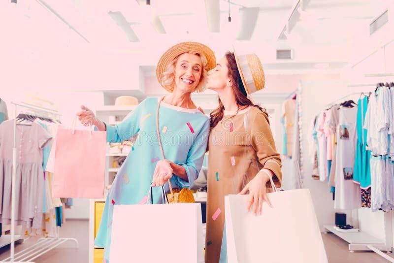 Dochter die haar moeder kussen terwijl het doen van samen het winkelen royalty-vrije stock afbeelding