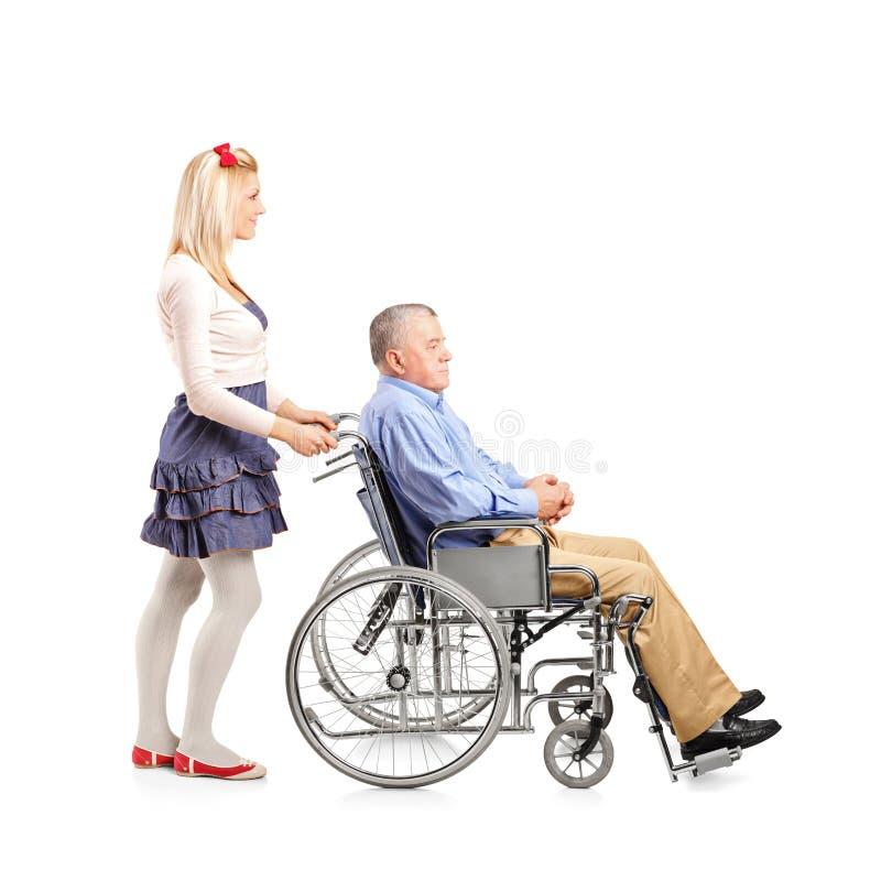 Dochter die haar papa in een rolstoel duwt royalty-vrije stock afbeelding
