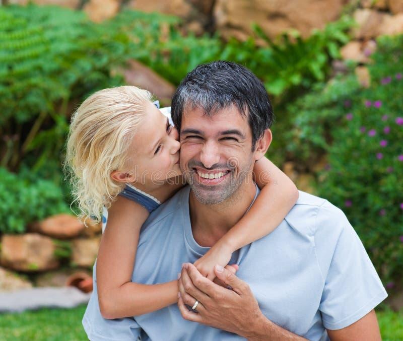 Dochter die haar vader kust stock afbeelding