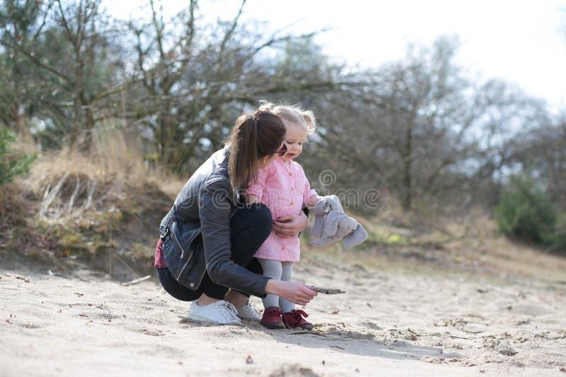 Dochter die met moeder in het zand babbelen stock foto's