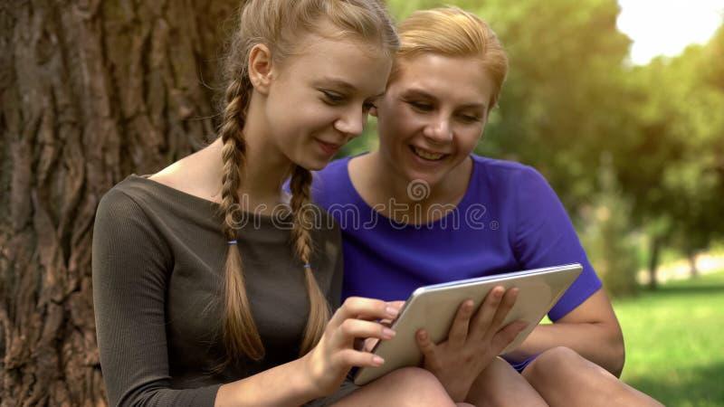 Dochter die moederfoto's van haar vriend tonen, die tablet, sociaal netwerken gebruiken royalty-vrije stock afbeelding